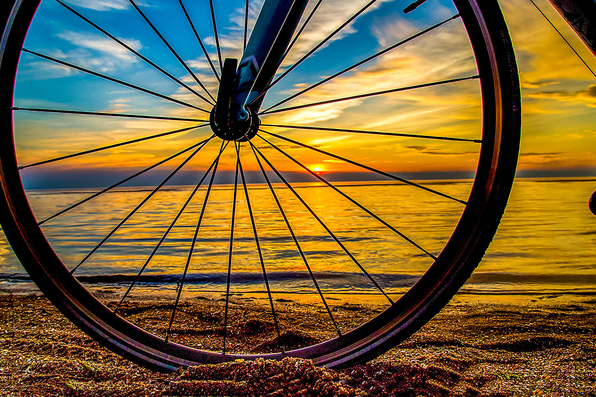 a bike wheel on the beach at sunset in Scotland